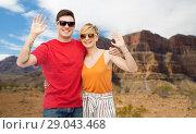 Купить «couple in sunglasses hugging and waving hands», фото № 29043468, снято 30 июня 2018 г. (c) Syda Productions / Фотобанк Лори