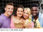 Купить «happy friends with takeaway food outdoors», фото № 29043520, снято 1 августа 2017 г. (c) Syda Productions / Фотобанк Лори