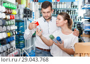 Купить «Ordinary man and woman choosing paint spray», фото № 29043768, снято 17 мая 2018 г. (c) Яков Филимонов / Фотобанк Лори