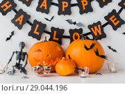 Купить «carved pumpkins with candies and halloween garland», фото № 29044196, снято 15 сентября 2017 г. (c) Syda Productions / Фотобанк Лори