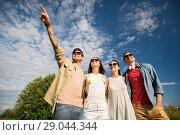 Купить «happy friends looking at something outdoors», фото № 29044344, снято 7 июля 2018 г. (c) Syda Productions / Фотобанк Лори