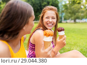 Купить «teenage girls eating ice cream at picnic in park», фото № 29044380, снято 19 июля 2018 г. (c) Syda Productions / Фотобанк Лори