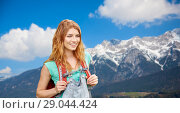 Купить «smiling woman with backpack over alps mountains», фото № 29044424, снято 25 июля 2015 г. (c) Syda Productions / Фотобанк Лори