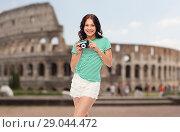 Купить «teenage girl with film camera over coliseum», фото № 29044472, снято 30 июня 2018 г. (c) Syda Productions / Фотобанк Лори