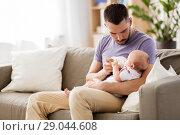 Купить «father feeding baby daughter from bottle at home», фото № 29044608, снято 16 мая 2018 г. (c) Syda Productions / Фотобанк Лори