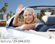 Купить «happy young woman in convertible car waving hand», фото № 29044672, снято 17 августа 2017 г. (c) Syda Productions / Фотобанк Лори