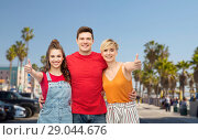Купить «happy friends showing thumbs up and hugging», фото № 29044676, снято 30 июня 2018 г. (c) Syda Productions / Фотобанк Лори