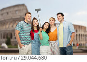 friends taking selfie by monopod over coliseum. Стоковое фото, фотограф Syda Productions / Фотобанк Лори
