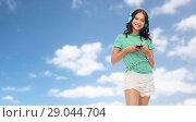 Купить «teenage girl in phones with smartphone over sky», фото № 29044704, снято 30 июня 2018 г. (c) Syda Productions / Фотобанк Лори