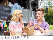 Купить «friends clinking drinks and eating at food truck», фото № 29044716, снято 1 августа 2017 г. (c) Syda Productions / Фотобанк Лори
