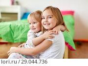 Купить «happy little girls or sisters hugging at home», фото № 29044736, снято 15 октября 2017 г. (c) Syda Productions / Фотобанк Лори