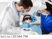 Купить «dentist treating kid teeth at dental clinic», фото № 29044796, снято 22 апреля 2018 г. (c) Syda Productions / Фотобанк Лори