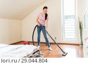 Купить «woman or housewife with vacuum cleaner at home», фото № 29044804, снято 29 апреля 2018 г. (c) Syda Productions / Фотобанк Лори