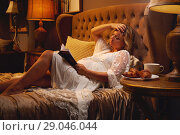 Купить «Pregnant young blond woman in rest gown lying on the bed at bedroom and reading a book about maternity or chicklit, womans novel at home. Relaxation, leisure, hobby lifestyle, free time habits concept», фото № 29046044, снято 24 августа 2018 г. (c) Alexander Tihonovs / Фотобанк Лори