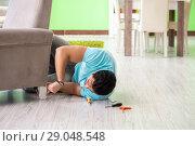 Купить «Man repairing furniture at home», фото № 29048548, снято 14 мая 2018 г. (c) Elnur / Фотобанк Лори