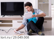 Купить «Man trying to fix broken tv», фото № 29049008, снято 9 марта 2018 г. (c) Elnur / Фотобанк Лори