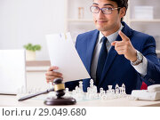 Купить «Young lawyer playing chess to train his court strategy and tacti», фото № 29049680, снято 31 июля 2018 г. (c) Elnur / Фотобанк Лори
