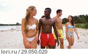 Купить «mixed race couple walking along beach with friends», видеоролик № 29050020, снято 24 августа 2018 г. (c) Syda Productions / Фотобанк Лори