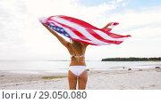 Купить «happy young woman with american flag on beach», видеоролик № 29050080, снято 24 августа 2018 г. (c) Syda Productions / Фотобанк Лори