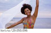 Купить «african woman with shawl waving in wind on beach», видеоролик № 29050096, снято 24 августа 2018 г. (c) Syda Productions / Фотобанк Лори