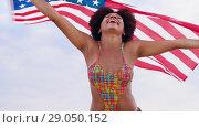 Купить «happy african woman with american flag on beach», видеоролик № 29050152, снято 24 августа 2018 г. (c) Syda Productions / Фотобанк Лори