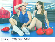 Купить «Female boxer is sitting with man and talking about healthy in gym.», фото № 29050588, снято 21 августа 2017 г. (c) Яков Филимонов / Фотобанк Лори