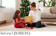 Купить «mother and daughter with christmas gift at home», видеоролик № 29050912, снято 31 августа 2018 г. (c) Syda Productions / Фотобанк Лори