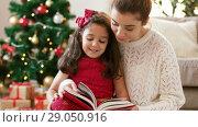 Купить «mother and daughter reading book at christmas», видеоролик № 29050916, снято 31 августа 2018 г. (c) Syda Productions / Фотобанк Лори