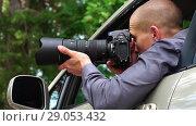 Купить «Spy Sits In Car Looking Around And Taking Photos», видеоролик № 29053432, снято 27 июня 2018 г. (c) Pavel Biryukov / Фотобанк Лори