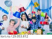 Купить «Boys and girls handing gifts to each other during dinner», фото № 29053812, снято 26 июня 2019 г. (c) Яков Филимонов / Фотобанк Лори