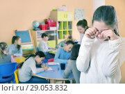 Купить «Upset girl in schoolroom on background with pupils», фото № 29053832, снято 28 января 2018 г. (c) Яков Филимонов / Фотобанк Лори