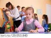 Купить «Girl drawing in schoolroom during break», фото № 29053840, снято 28 января 2018 г. (c) Яков Филимонов / Фотобанк Лори