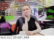 Купить «Девушка с мобильным телефоном в кафе», фото № 29061944, снято 26 августа 2018 г. (c) Victoria Demidova / Фотобанк Лори