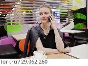Купить «Девушка с мобильным телефоном в кафе», фото № 29062260, снято 26 августа 2018 г. (c) Victoria Demidova / Фотобанк Лори