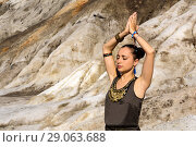 Young beautiful woman stands with arms raised over her head, in a namaste position, outdoor against a background of desert rocks. Стоковое фото, фотограф Евгений Харитонов / Фотобанк Лори