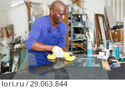 Купить «professional African American glazier choosing glass for cutting in workshop», фото № 29063844, снято 16 мая 2018 г. (c) Яков Филимонов / Фотобанк Лори