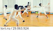 Купить «adults and teenagers athletes at fencing workout», фото № 29063924, снято 30 мая 2018 г. (c) Яков Филимонов / Фотобанк Лори