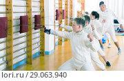 Купить «Sports group of athletes at fencing workout», фото № 29063940, снято 30 мая 2018 г. (c) Яков Филимонов / Фотобанк Лори