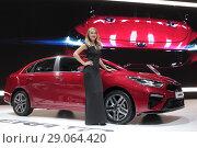 Купить «Новый КИА церато на стенде автосалона и девушка в черном платье в Москве», эксклюзивное фото № 29064420, снято 9 сентября 2018 г. (c) Дмитрий Неумоин / Фотобанк Лори