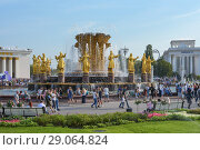 Купить «Moscow, Russia - September 8, 2018: People walk on VDNH on a festive summer day on the background of the fountain of Friendship of  nations», фото № 29064824, снято 8 сентября 2018 г. (c) Ирина Носова / Фотобанк Лори