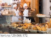 Купить «Smiling women selling fresh pastry and loaves», фото № 29066172, снято 21 октября 2018 г. (c) Яков Филимонов / Фотобанк Лори