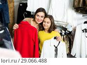 Купить «Mother and daughter examining various blouses», фото № 29066488, снято 22 сентября 2018 г. (c) Яков Филимонов / Фотобанк Лори