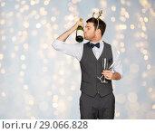 Купить «man kissing bottle of champagne at christmas party», фото № 29066828, снято 15 декабря 2017 г. (c) Syda Productions / Фотобанк Лори