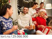 Купить «friends celebrating christmas and opening presents», фото № 29066900, снято 17 декабря 2017 г. (c) Syda Productions / Фотобанк Лори