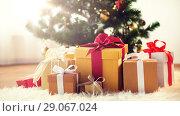 Купить «gift boxes on sheepskin at christmas tree», фото № 29067024, снято 7 сентября 2017 г. (c) Syda Productions / Фотобанк Лори