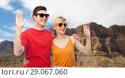 Купить «couple in sunglasses hugging and waving hands», фото № 29067060, снято 30 июня 2018 г. (c) Syda Productions / Фотобанк Лори