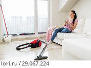 Купить «woman with vacuum cleaner drinking coffee at home», фото № 29067224, снято 29 апреля 2018 г. (c) Syda Productions / Фотобанк Лори