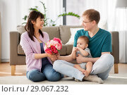 Купить «happy family with flowers and baby boy at home», фото № 29067232, снято 5 мая 2018 г. (c) Syda Productions / Фотобанк Лори