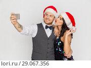 Купить «couple in santa hats aking selfie at christmas», фото № 29067356, снято 15 декабря 2017 г. (c) Syda Productions / Фотобанк Лори