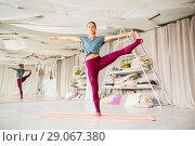 woman doing yoga hand-to-big-toe pose at studio. Стоковое фото, фотограф Syda Productions / Фотобанк Лори
